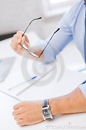 Businessman with spectacles writing in notebook