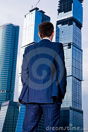Businessman standing back against skyscraper