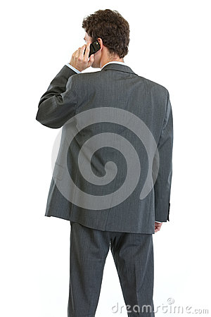 Businessman standing back and speaking mobile