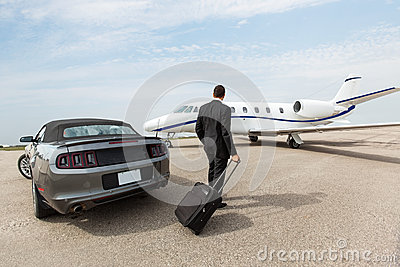 Businessman Standing By Car And Private Jet At