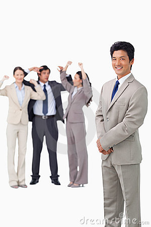 Businessman standing with cheering team behind him