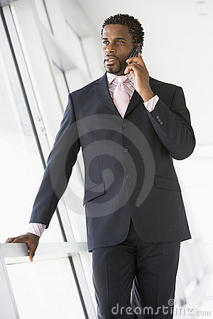 Businessman standing in corridor using a mobile