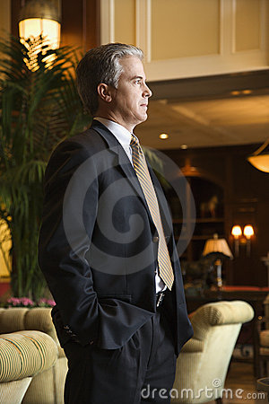 Businessman standing in hotel lobby.