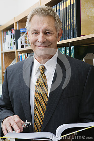 Businessman Standing In Library With Book