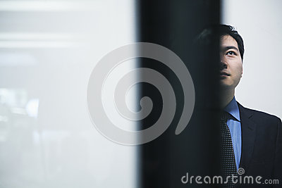 Businessman standing and looking up parking garage, white background