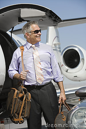 Businessman Standing With Luggage At Airfield