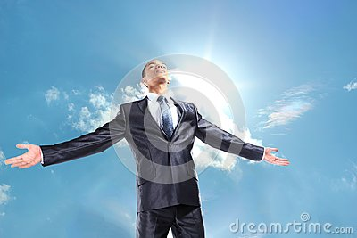 Businessman standing outside with arms outstretched