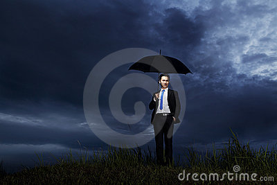 Businessman standing with umbrella