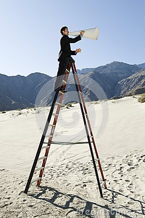 Businessman On Stepladder Using Megaphone In Desert