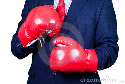 Businessman in suit  boxing in red gloves.