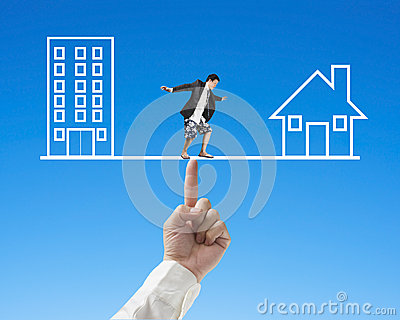 Businessman surfing on seesaw with Office and home, balance conc