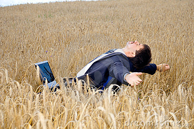 Businessman takes a rest in field