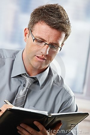 Businessman taking notes into organiser