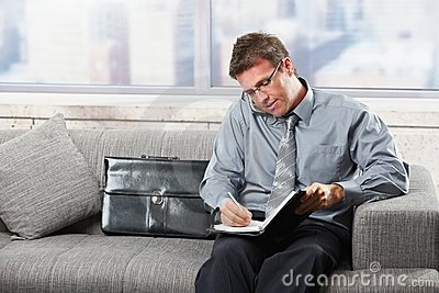 Businessman taking notes on sofa
