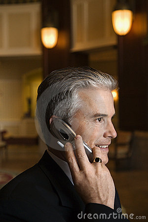 Businessman talking on cellphone in hotel lobby.