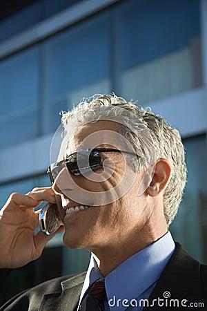 Businessman talking on cellphone in urban setting.