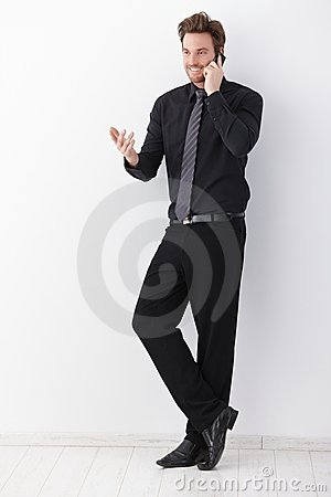 Businessman talking on mobile phone smiling