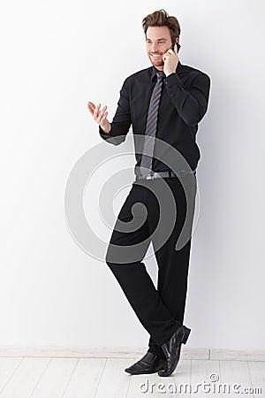 Businessman talking on mobile phone smiling