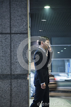 Businessman talking on the phone in a parking garage