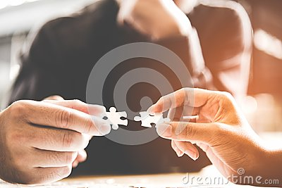 Businessman team work holding two jigsaw connecting couple puzzle piece for matching to goals target, success and start up new pro Stock Photo