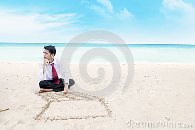 Businessman thinking at a beach