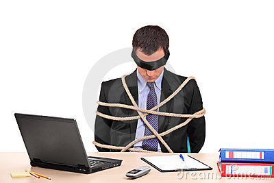 A businessman tied up with rope in his office