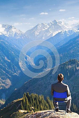 Businessman at the top of mountain is thinking