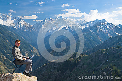 Businessman at top of mountain using his laptop
