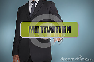 Businessman touching the word motivation written on green tag