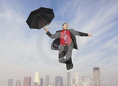 Businessman With An Umbrella In Midair
