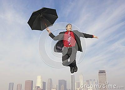 Businessman With An Umbrella In Midair