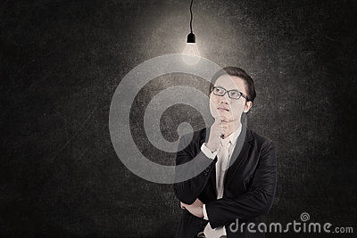 Businessman under lit bulb thinking of idea