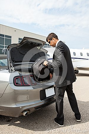 Businessman Unloading Luggage From Car At Airport