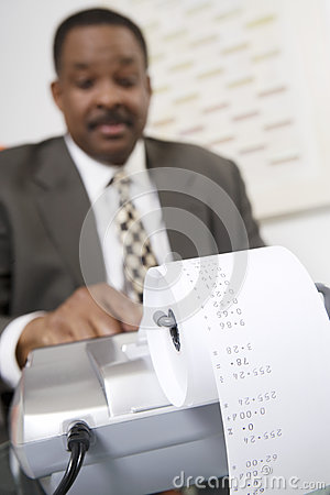 Businessman Using an Adding Machine