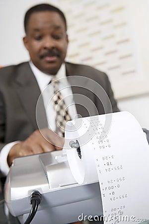 Businessman Using an Adding Machine