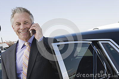 Businessman Using Cellphone Standing By Car