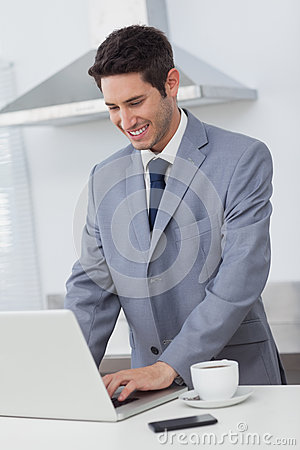 Businessman using his laptop while having breakfast