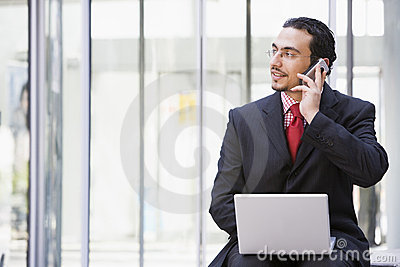Businessman using laptop and mobile phone outside