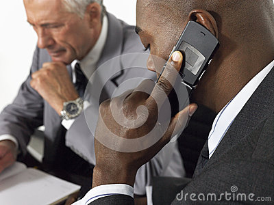 Businessman Using Mobile Phone In Meeting