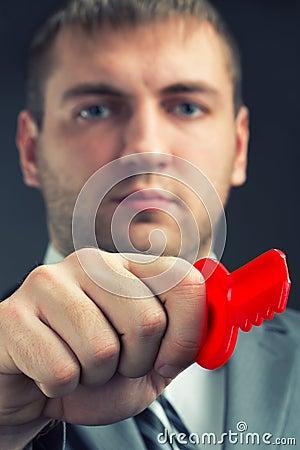 Businessman using red toy key