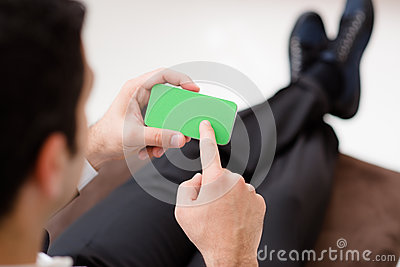 Businessman using smartphone with green screen