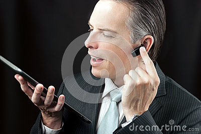 Businessman Using Tablet & Headset Earpiece.