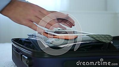 Businessman Verifique o conteúdo da mala usando um tablet tátil preparando-se para uma viagem filme