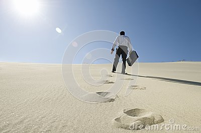 Businessman Walking With Briefcase In Desert