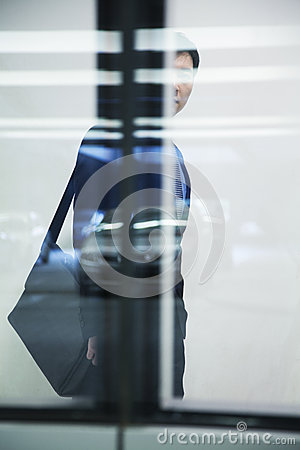 Businessman walking with briefcase in parking garage, white background