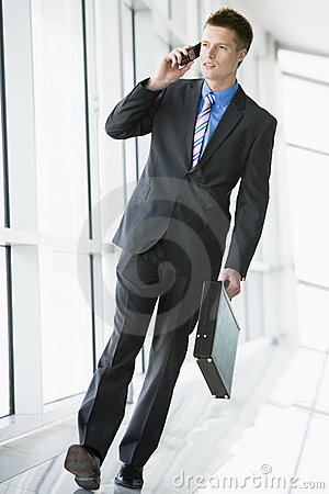 Businessman walking in corridor using mobile phone