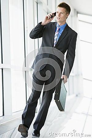 Businessman walking in corridor using mobile phone