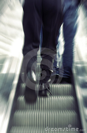 Businessman walking on escalator