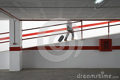 Businessman Walking Up Ramp With Luggage In Parking Garage