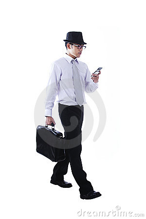 Businessman walking while using mobile phone